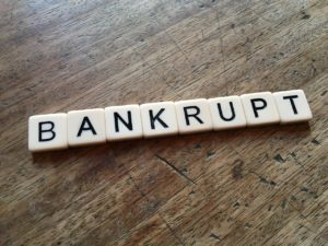 The word 'bankrupt' spelled out in Scrabble tiles, indicating that bankruptcy (like a game) can be an energizing experience to solve money troubles.