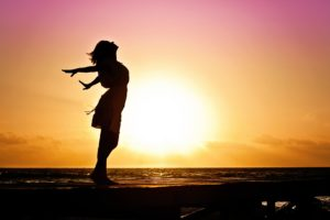 Silhouette of a woman experiencing debt freedom for the first time, arms outstretched behind her, enjoying the sunrise. Money troubles are behind her.