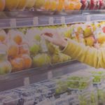Woman in yellow jacket grocery shopping