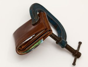 A wallet being squeezed shut by a C-Clamp, indicating money problems.