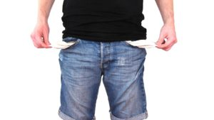 Man with money troubles pulling the lining of his empty pant pockets inside out to show nothing is there.