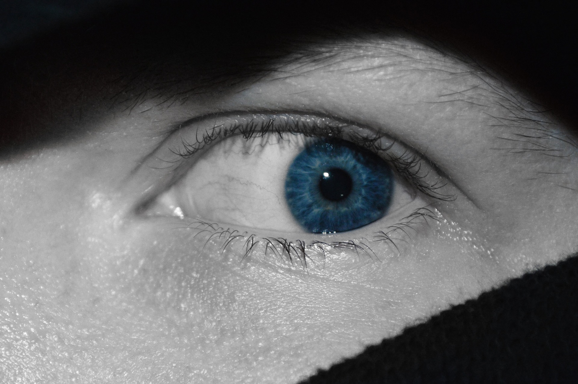 The scared blue eye of a person hiding behind a shadowy object in the dark.